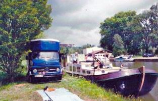 Laster und Hausboot nebeneinander im Hafen